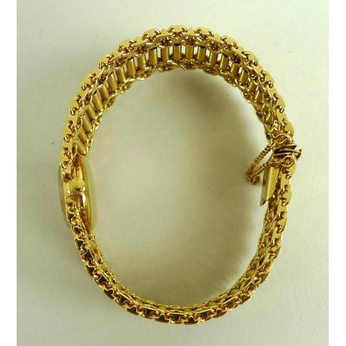 880 - A Longines lady's 18K gold cased wristwatch, champagne enamel circular dial bearing gilt batons, ref...
