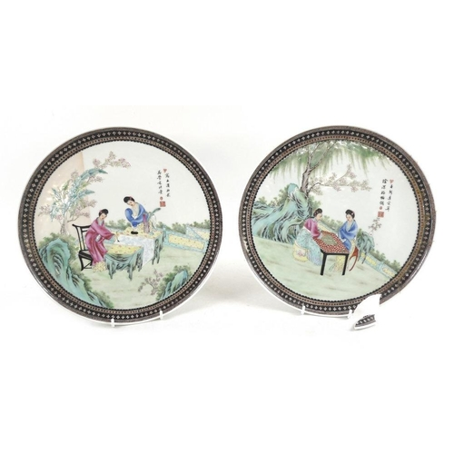 502 - A pair of Chinese Republic period porcelain plates, decorated with two ladies at different artistic ...
