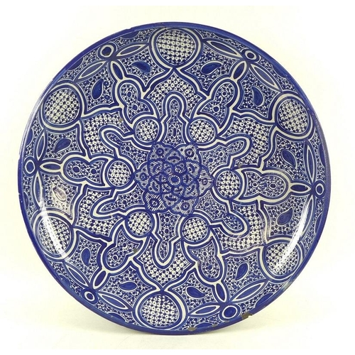 519 - A large 19th century earthenware charger, likely Spanish, the interior of the bowl painted with intr...