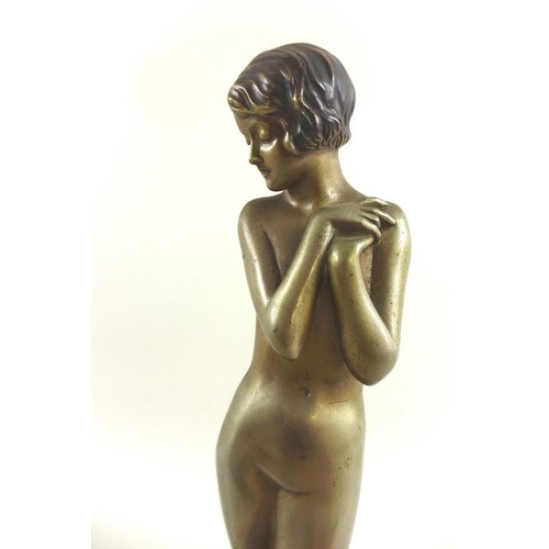 717 - An Art Deco sculpture of a bronze model of a coy maiden, the nude figure modelled standing, after Jo...