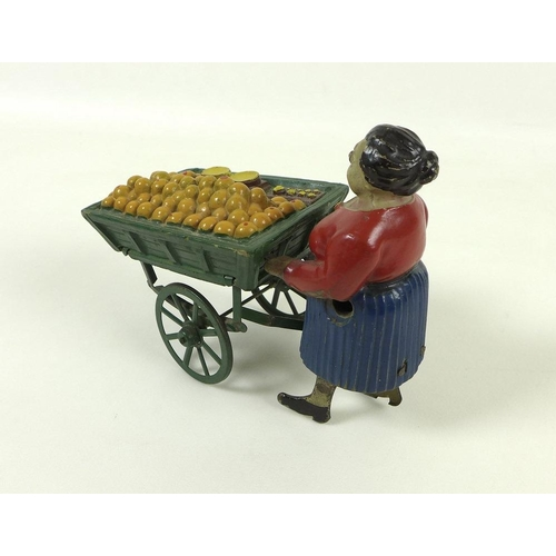 583 - A tin and composition clockwork toy figure, early 20th century, modelled as an orange seller with ca...