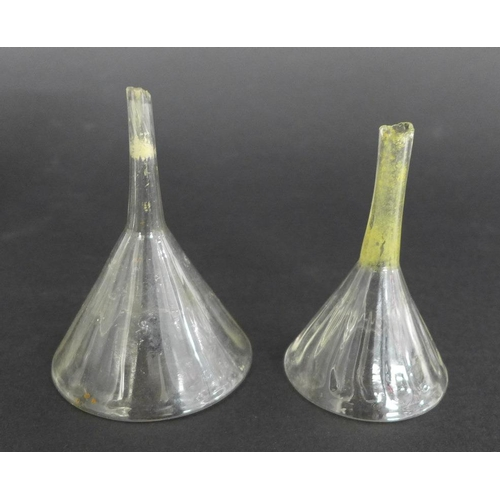 691 - Two small Georgian glass wine funnels with lobed detailing, together with two corkscrews and a glass...