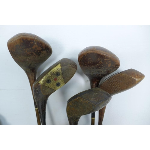 693 - A selection of early 20th century golf clubs, several hickory shafted, comprising 11 woods, 12 irons...