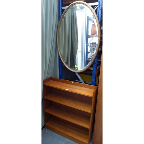 29 - A modern mahogany freestanding bookcase, 76.5 by 20.5 by 88cm high, together with an oval wall mirro...