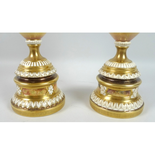 43 - A pair of modern Royal Worcester pedestal vases, foliate clasped twin handles, decorated in a 'Hand ...