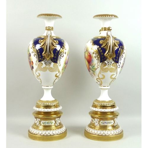 45 - A pair of large modern Royal Worcester pedestal vases, foliate clasped twin handles, decorated in a ...