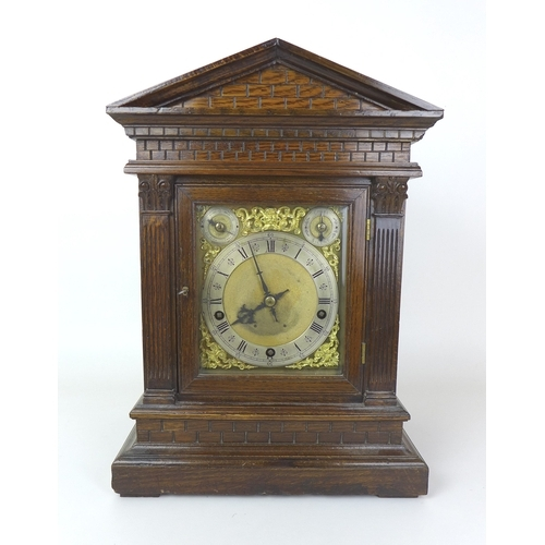 77 - A late Victorian oak cased mantel clock, with musical movement stamped 'W+H SGL' chiming on four coi...