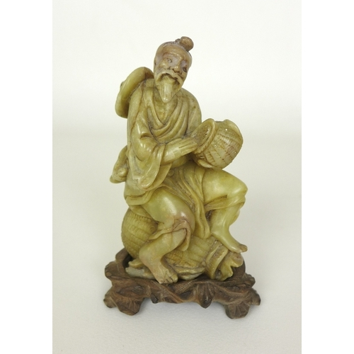 78 - A Chinese carved figure of a smiling fisherman, possibly jade, sitting on one basket whilst holding ...