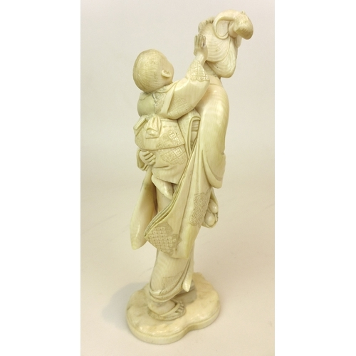 86 - A late 19th century Japanese carved ivory figure of a mother and child, the kimonos of each carved w...