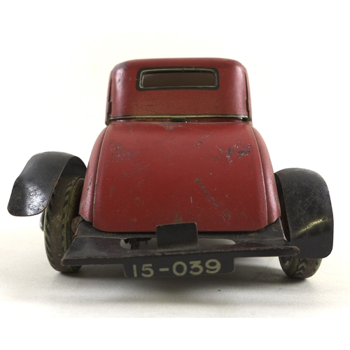 129 - A Burnett Ltd London clockwork tin plate saloon car, in red and black, with tin plate tyres, 25.5cm ...