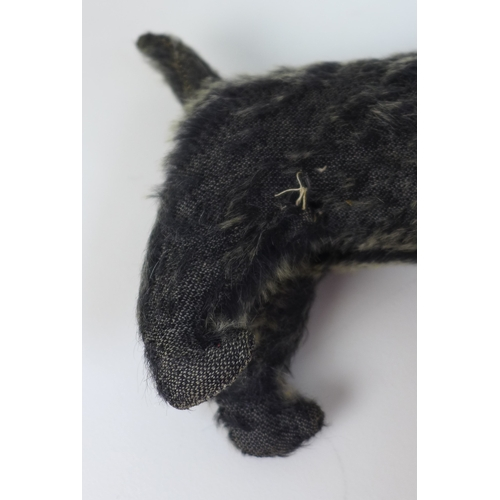 113 - A Peacocks soft toy dog, circa 1930, with dark grey plush hair, sewn nose, and one remaining eye, la...