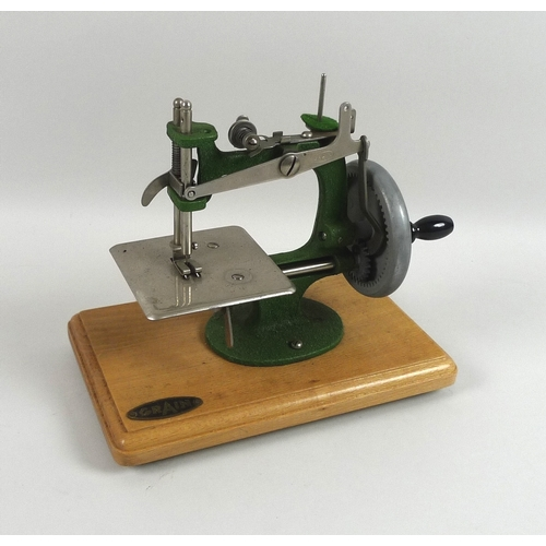 109 - A Grain miniature toy sewing machine with green metal body, on wooden base, 18cm high, with original...