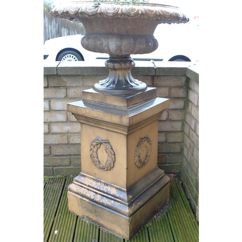 190 - A buff terracotta Campana style pedestal urn, with lobed rim, on a square section pedestal base with...