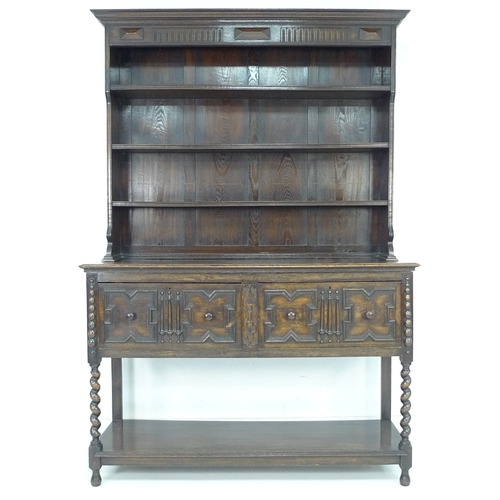 202 - A mid 20th century oak dresser with two shelf plate rack, two panelled doors with an undertier unite...
