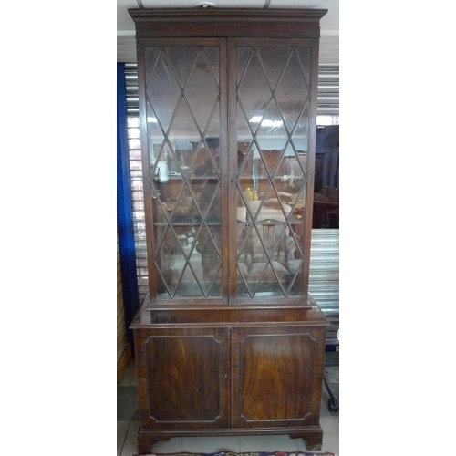 247 - An early 19th century mahogany bookcase, with unusually tall astragal diamond paned glazed doors enc...