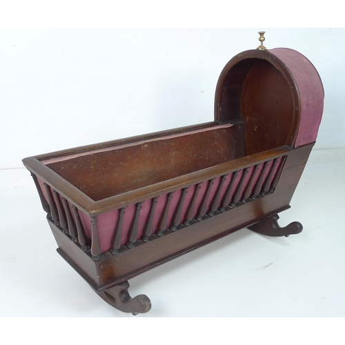 234 - A Victorian mahogany rocking crib, with turned spindle sides, hood to one end with brass thistle fin...