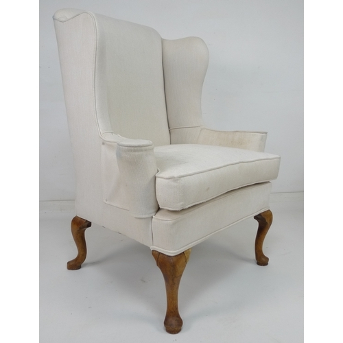 213 - A wing back armchair, with high back and outswept arms, raised on cabriole legs, recently upholstere...