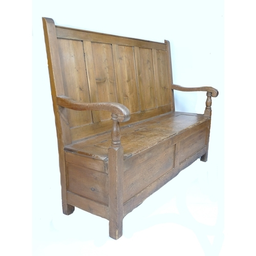 214 - A Victorian pine settle, with five panel back, scroll end open arms supported on turned columns, the...