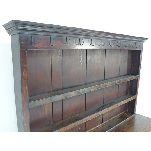 263 - A George III oak dresser, with two shelf plate rack, original metal hooks, three frieze drawers with...