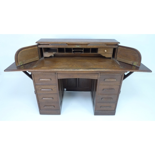 218 - An early 20th century oak roll top desk, with unusual hinged wings and drop leaves to either end, fi...