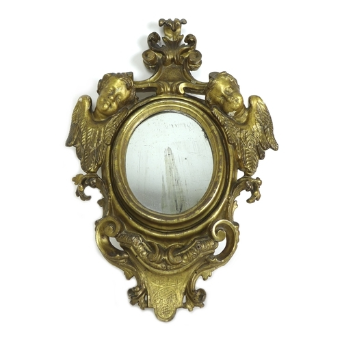 256 - A small Italian 18th / 19th century giltwood wall mirror, with small oval plate, the frame carved wi...