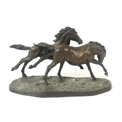 81 - A Heredities bronzed resin sculpture of two stallions running wild, on a naturalistic oval base, num...
