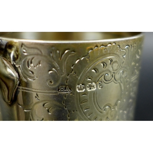 62 - A Victorian silver christening mug, the body foliate engraved around cartouche inscribed JPT 1894 fr...