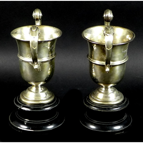 29 - A pair of silver twin handled golf trophies, flying scroll handles to knopped urnular bodies, with i...