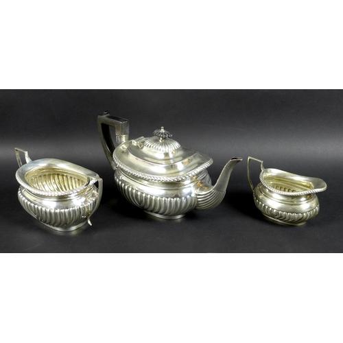 69 - An Edwardian three piece silver tea set, comprising tea pot, milk jug and sucrier, boat shaped bodie...