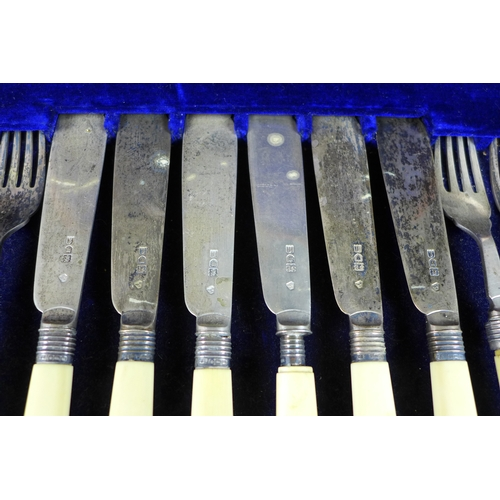 51 - A set of Edward VII silver fish eaters, twelve place settings of knives and forks, with ivory handle...