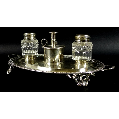 73 - A George III and Victorian silver desk stand of oval twin handled form, with swag decoration within ...