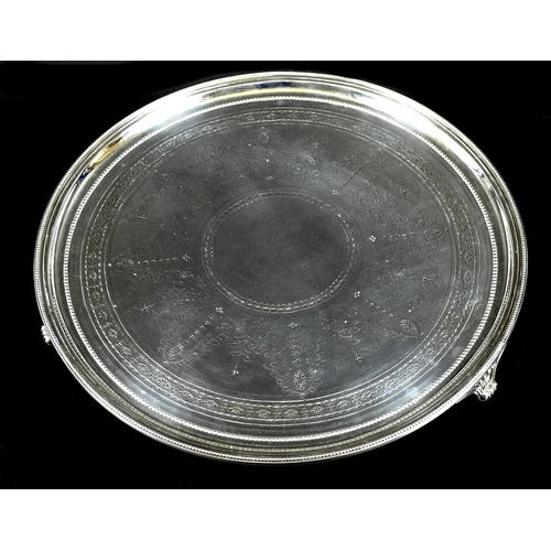 75 - A large Victorian silver salver, the body engraved with foliate swags and drapery, beaded rim and th...