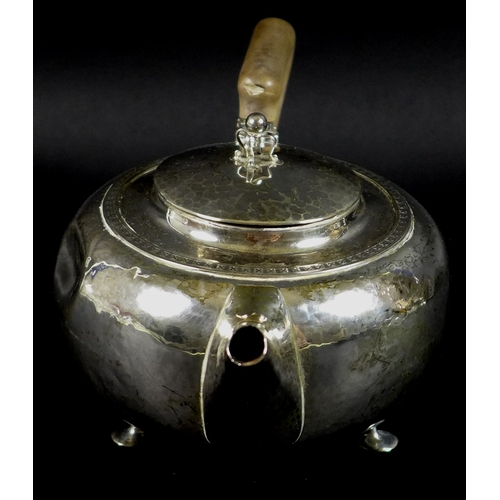 37 - An Arts & Crafts silver teapot, of squat ovoid form with shaped handle and raised on three feet, Alb...