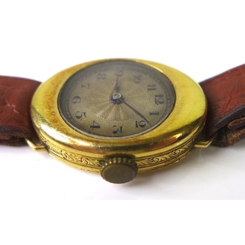 120 - An early 20th century 18ct gold lady's watch in unusual oval shaped case with engraved scroll detail...