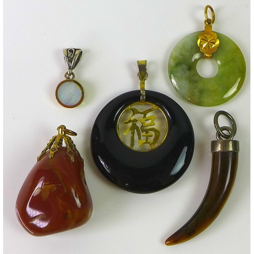 129 - A group of five pendants, comprising a late 20th century Jade bidisk, a Jet pendant similar, inset w...