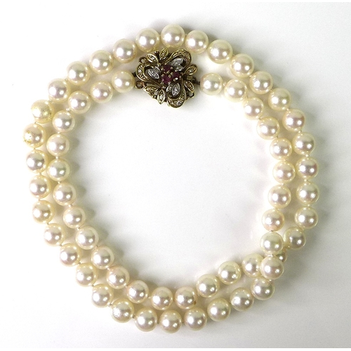 105 - A string of pearls, the 9ct gold clasp set with rubies and diamond chips, hallmarked, 30.2g....
