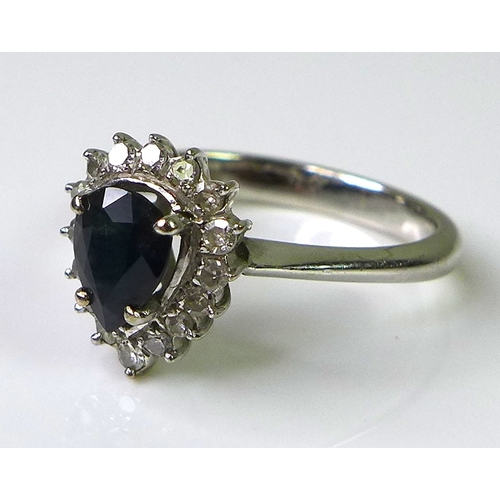 240 - An 18ct white gold, sapphire and diamond dress ring, with pear cut central sapphire of approximately...