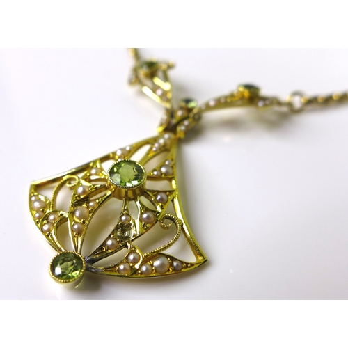 104 - A 14ct gold Edwardian style pendant set with seed pearls and peridots, pierced chandelier form, mark...