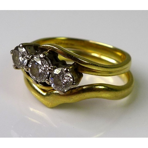 247 - An 18ct gold three stone diamond ring, the central diamond of approx 0.25cts flanked by two diamonds...