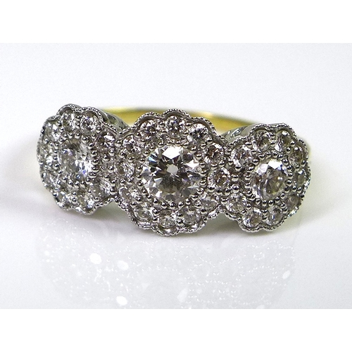 243 - A 18ct gold and diamond ring, the three main diamonds encircled by diamond chips to form three flowe...