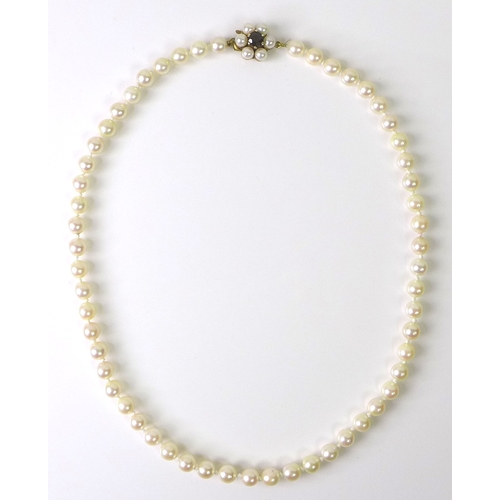 146 - A Japanese Mikimoto cultured pearl necklace, the 9ct gold clasp set with central garnet and further ...