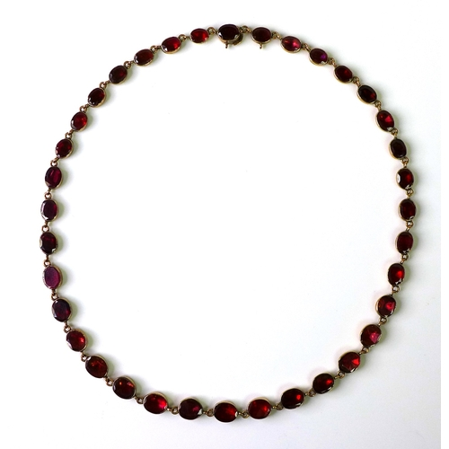 229 - An 18th/19th century rose gold and red stone riviere necklace, the stones possibly garnets, oval cut...