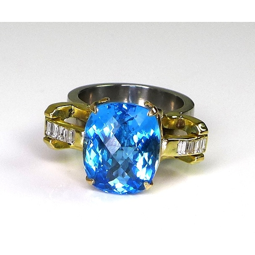 258 - A modern designer ring set with large chequerboard cut blue topaz on palladium shank, the 18ct gold ...