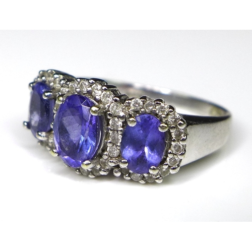 242 - An 18ct white gold, tanzanite and diamond ring, the three oval cut tanzanites surrounded by 40 diamo...