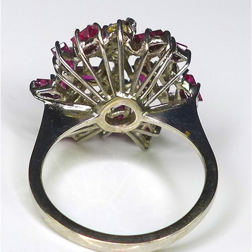 254 - A diamond and ruby dress ring of asymmetrical cluster form, set in white gold or platinum, composed ...