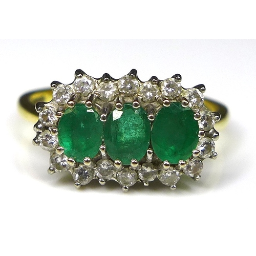 210 - An 18ct gold, emerald and diamond ring, the three oval cut emeralds each of 5 by 4mm surrounded by 1...