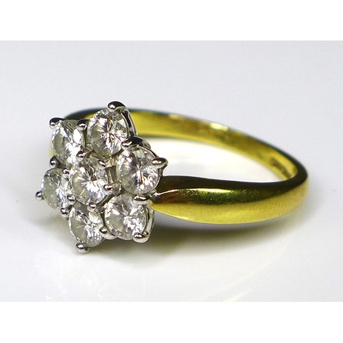 256 - An 18ct gold and diamond flowerhead ring, the seven diamonds each of approximately 0.2ct, total diam...