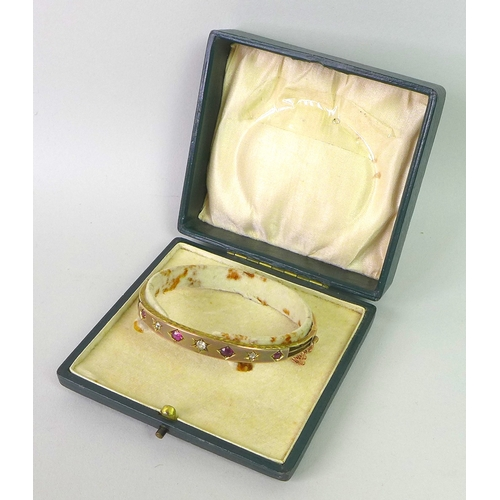 205 - A Victorian 9ct gold, diamond and ruby bangle, set with four rubies and three diamonds, each within ...