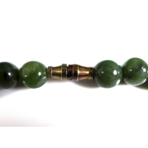 119 - A string of fifty five jade beads, on a yellow metal screw clasp, each approx 8.3mm, 41cm....