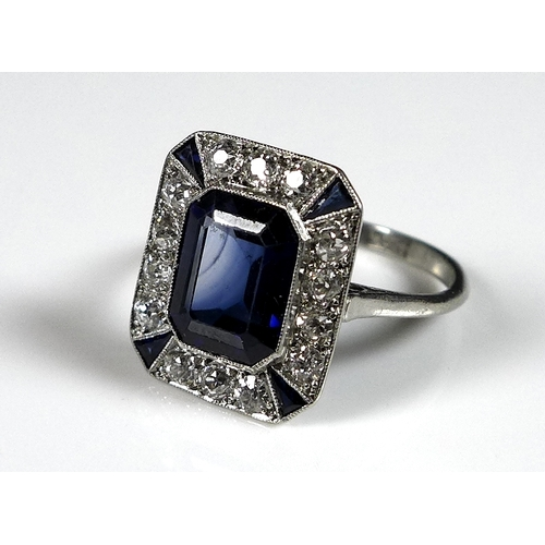 154 - An Art Deco style sapphire and diamond dress ring, with central emerald cut stone, 9 by 7 by 4.5mm, ...